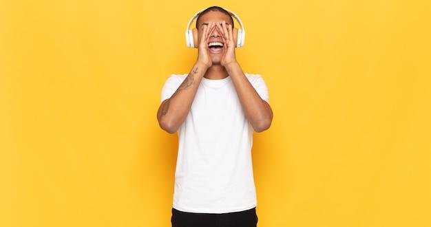 Giovane uomo di colore che si sente felice, eccitato e positivo, dando un grande grido con le mani vicino alla bocca, chiamando