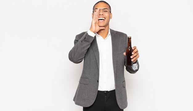 Giovane uomo di colore che si sente felice, eccitato e positivo, gridando con le mani vicino alla bocca
