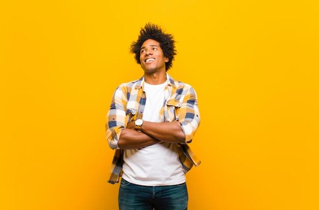 Giovane uomo di colore sentirsi felice, orgoglioso e pieno di speranza, chiedendosi o pensando, alzando lo sguardo per copiare lo spazio con le braccia incrociate contro il muro arancione