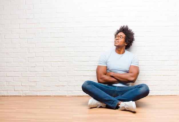 Giovane uomo nero sentirsi felice, orgoglioso e pieno di speranza, chiedendosi o pensando, alzando lo sguardo per copiare lo spazio con le braccia incrociate seduto sul pavimento a casa