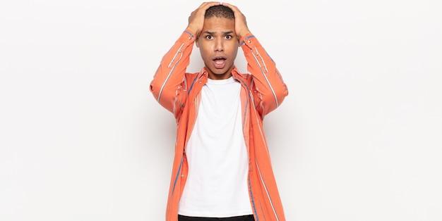 Giovane uomo di colore che si sente inorridito e scioccato, alza le mani alla testa e si fa prendere dal panico per un errore