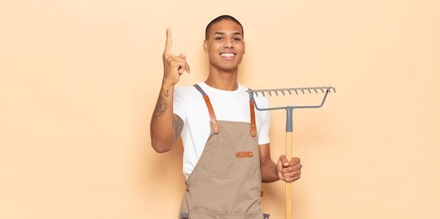 Giovane uomo di colore che si sente come un genio felice ed eccitato dopo aver realizzato un'idea, alzando allegramente il dito, eureka!