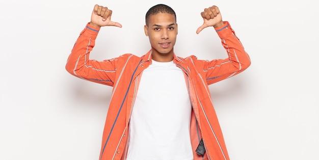 Giovane uomo di colore che si sente orgoglioso, arrogante e fiducioso, sembra soddisfatto e di successo, indicando se stesso