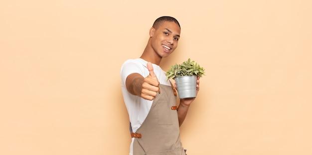 Giovane uomo di colore che si sente orgoglioso, spensierato, fiducioso e felice, sorridendo positivamente con i pollici in su
