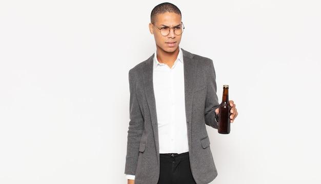 Giovane uomo di colore che si sente triste, turbato o arrabbiato e guarda di lato con un atteggiamento negativo, aggrottando la fronte in disaccordo