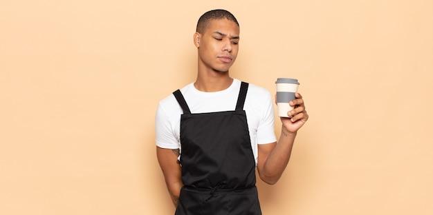 Giovane uomo di colore che si sente triste, turbato o arrabbiato e guarda di lato con un atteggiamento negativo, accigliato in disaccordo
