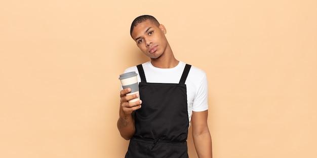 Giovane uomo di colore che si sente triste e piagnucoloso con uno sguardo infelice, piange con un atteggiamento negativo e frustrato