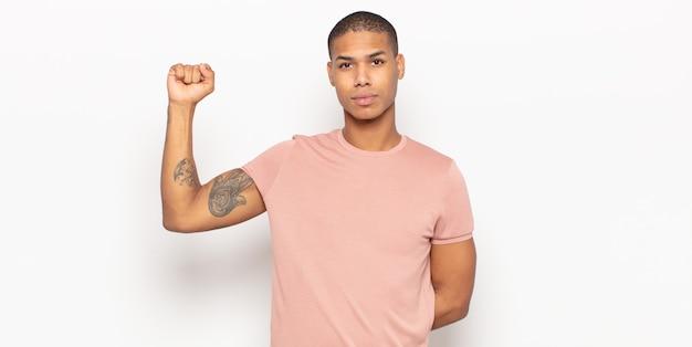 Giovane uomo di colore che si sente serio, forte e ribelle, alza il pugno, protesta o combatte per la rivoluzione