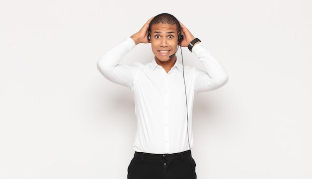 Giovane uomo di colore che si sente stressato, preoccupato, ansioso o spaventato, con le mani sulla testa, in preda al panico per errore