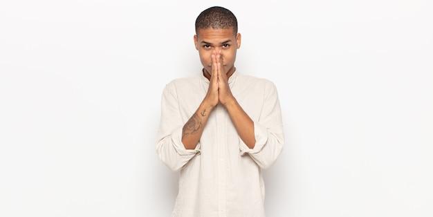 Giovane uomo di colore che si sente preoccupato, fiducioso e religioso, pregando fedelmente con i palmi premuti, chiedendo perdono