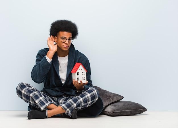 Il giovane uomo di colore che tiene un modello della casa che si siede sul pavimento prova ad ascoltare un gossip