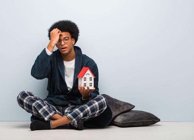 Giovane uomo di colore che tiene un modello di casa seduto sul pavimento preoccupato e sopraffatto