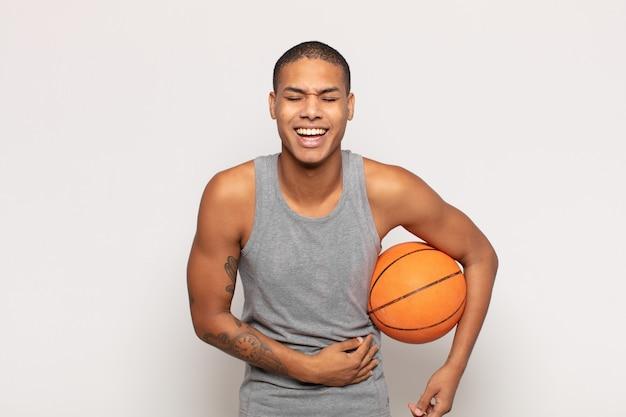 Giovane uomo di colore che ride ad alta voce per uno scherzo esilarante