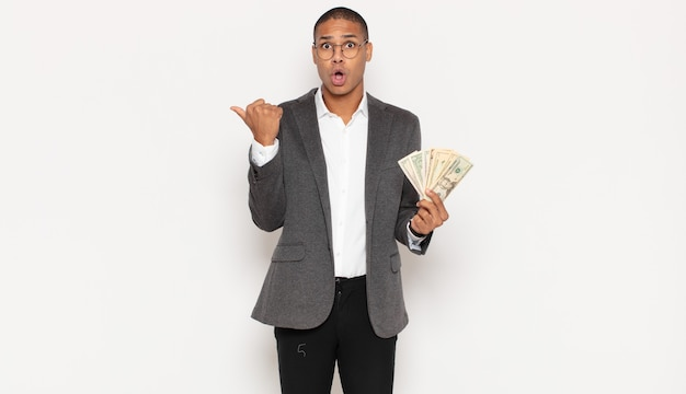 Giovane uomo di colore che guarda sbalordito incredulo, indicando un oggetto sul lato e dicendo wow, incredibile