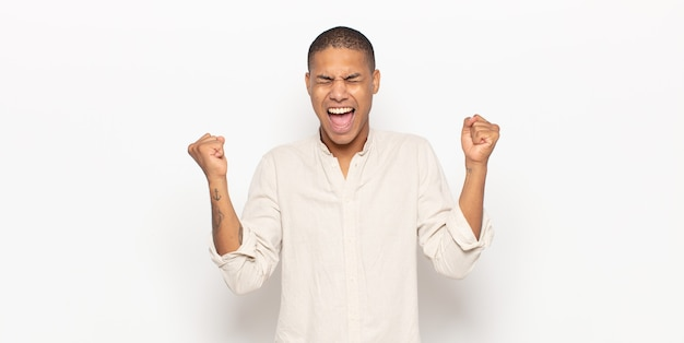 Giovane uomo di colore che sembra estremamente felice e sorpreso, celebrando il successo, gridando e saltando