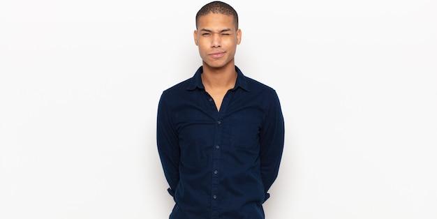 Giovane uomo di colore che sembra felice e amichevole, sorridente e ammiccante con un atteggiamento positivo