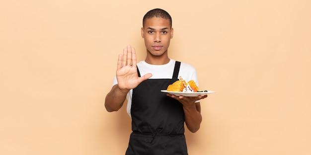 Giovane uomo di colore che sembra serio, severo, dispiaciuto e arrabbiato mostrando il palmo aperto che fa il gesto di arresto
