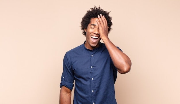 Giovane uomo di colore che sembra scioccato e stupito, con la bocca aperta per la sorpresa quando realizza qualcosa di incredibile