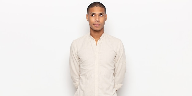Giovane uomo di colore che sembra preoccupato, stressato, ansioso e spaventato, in preda al panico e stringendo i denti