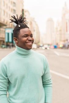 Giovane uomo di colore nel mezzo della città, sorridente. messa a fuoco selettiva.