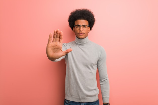 Giovane uomo di colore sopra un muro rosa mettendo la mano davanti