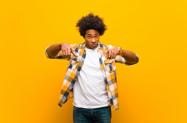 Giovane uomo di colore che punta in avanti alla fotocamera con entrambe le dita e l'espressione arrabbiata, che ti dice di fare il tuo dovere contro il muro arancione