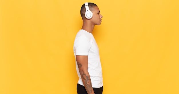 Giovane uomo di colore sulla vista di profilo che cerca di copiare lo spazio avanti, pensare, immaginare o sognare ad occhi aperti