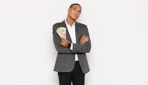 Giovane uomo di colore che scrolla le spalle, sentendosi confuso e incerto, dubitando con le braccia incrociate e lo sguardo perplesso