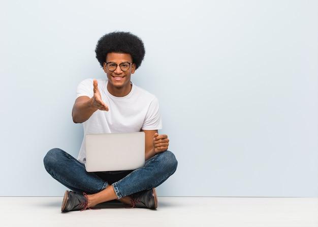 Giovane uomo di colore che si siede sul pavimento con un computer portatile che raggiunge fuori per accogliere qualcuno