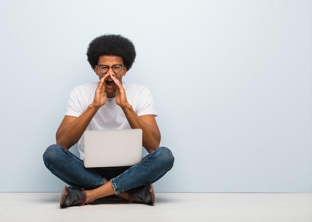 Giovane uomo di colore che si siede sul pavimento con un computer portatile che grida qualcosa di felice alla parte anteriore