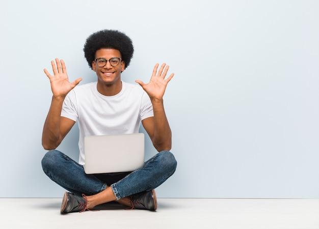 Giovane uomo di colore seduto sul pavimento con un computer portatile che mostra il numero dieci