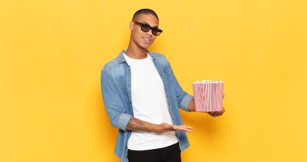 Giovane uomo di colore che sorride allegramente, sentendosi felice e mostrando un concetto nello spazio della copia con il palmo della mano
