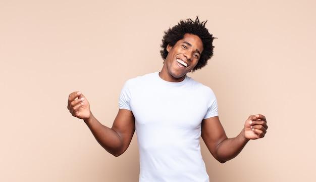 Giovane uomo di colore sorridente felicemente con faccia buffa, scherzando e guardando attraverso lo spioncino, spiando i segreti