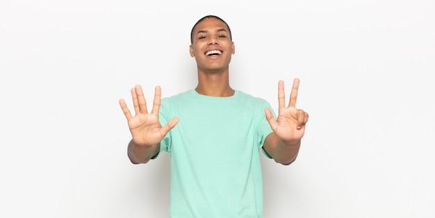Giovane uomo di colore che sorride e sembra amichevole, mostrando il numero otto o ottavo con la mano in avanti, contando alla rovescia