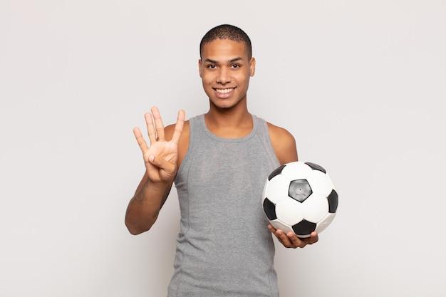 Giovane uomo di colore che sorride e sembra amichevole, mostrando il numero quattro o il quarto con la mano in avanti, contando alla rovescia