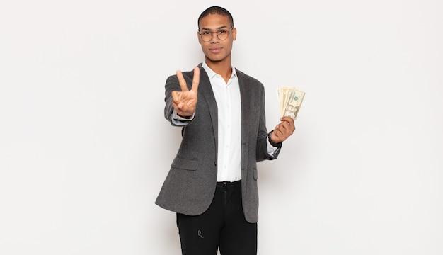 Giovane uomo di colore che sorride e sembra felice, spensierato e positivo, gesticolando vittoria o pace con una mano