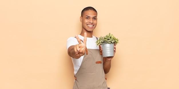 Giovane uomo di colore sorridente e felice, spensierato e positivo, gesticolando vittoria o pace con una mano
