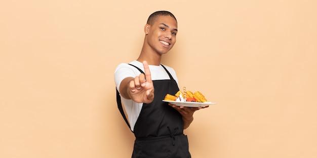 Giovane uomo di colore che sorride con orgoglio e sicurezza mentre posa trionfante il numero uno, sentendosi come un leader