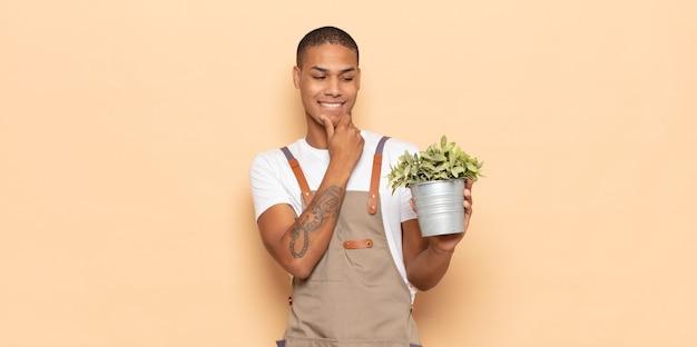 Giovane uomo di colore che sorride con un'espressione felice e sicura con la mano sul mento, chiedendosi e guardando di lato