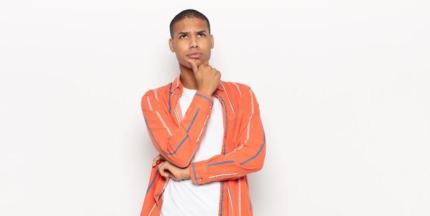 Giovane uomo di colore che pensa, si sente dubbioso e confuso, con diverse opzioni, chiedendosi quale decisione prendere