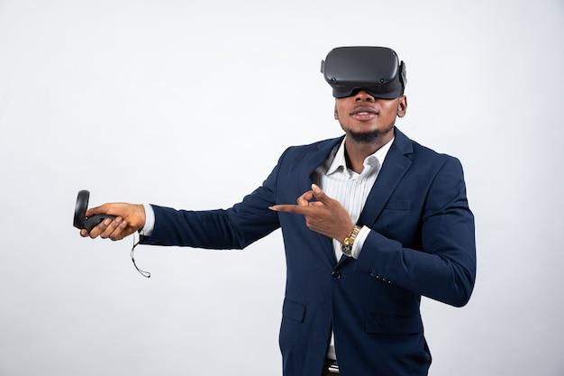 Giovane uomo di colore che usa un auricolare vr e un joystick