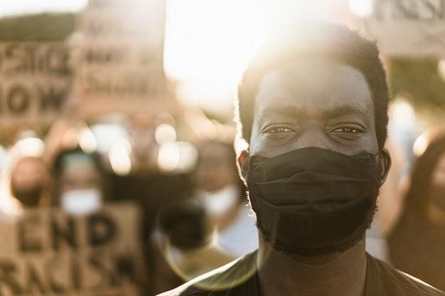 Giovane uomo di colore che indossa la maschera per il viso durante la protesta per la parità dei diritti