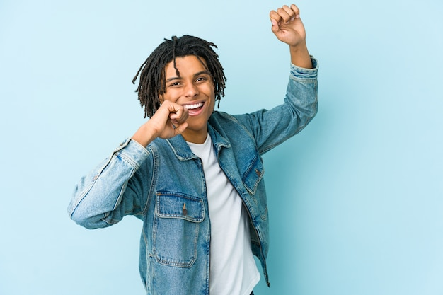 Giovane uomo di colore che indossa una giacca di jeans ballando e divertendosi.