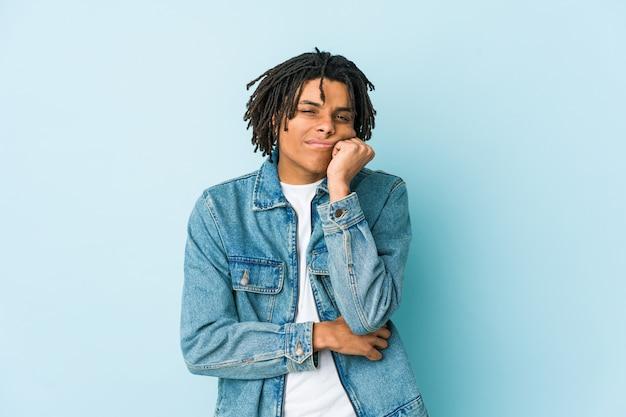 Giovane uomo di colore che indossa una giacca di jeans che si sente triste e pensieroso, guardando lo spazio della copia