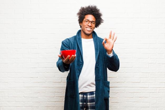 Pigiama da portare del giovane uomo di colore con una ciotola di prima colazione contro il br