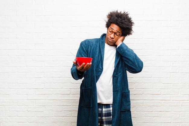 Pigiama da portare del giovane uomo di colore con una ciotola di prima colazione