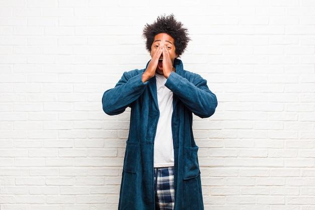 Giovane uomo di colore che indossa un pigiama con abito felice, eccitato e positivo, dando un grande grido con le mani vicino alla bocca, gridando contro il muro di mattoni