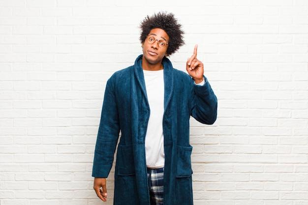 Giovane uomo di colore che indossa un pigiama con abito che sembra un genio che tiene orgogliosamente il dito in aria dopo aver realizzato una grande idea, dicendo eureka contro il muro di mattoni