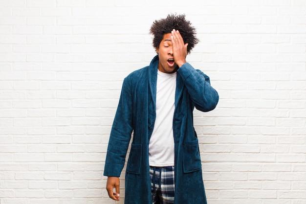 Giovane uomo di colore che indossa un pigiama con abito dall'aspetto assonnato, annoiato e sbadigliante, con un mal di testa e una mano che copre metà del viso contro il muro di mattoni