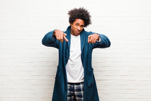 Giovane uomo di colore che indossa un pigiama con abito che punta in avanti con entrambe le dita e l'espressione arrabbiata, che ti dice di fare il tuo dovere contro il mattone